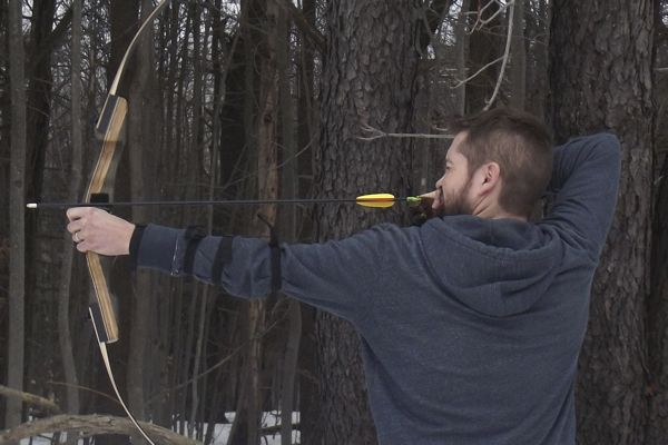Scott engages in some target practice with his bow and arrow—he hopes to get his daughters interested in the sport of archery.